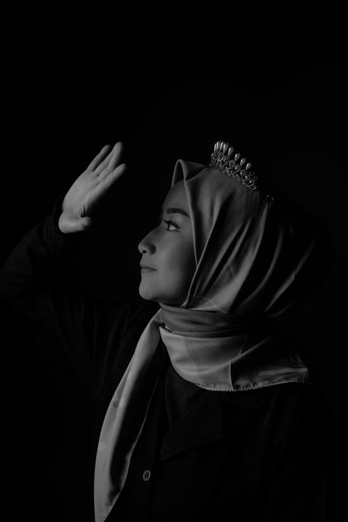 Graceful young ethnic woman with headscarf covering eyes with hand