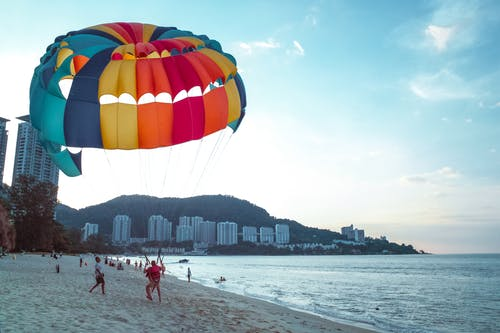 Man Riding Parachute on the Beach