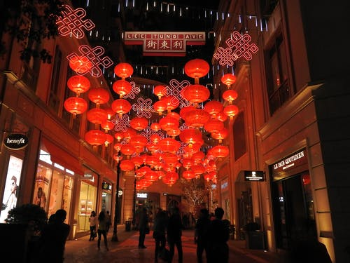 Traditional Chinese lanterns hanging in street between buildings with people