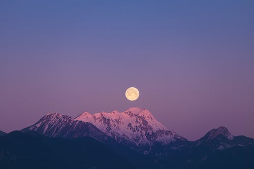 Full Moon over Snow Covered Mountain