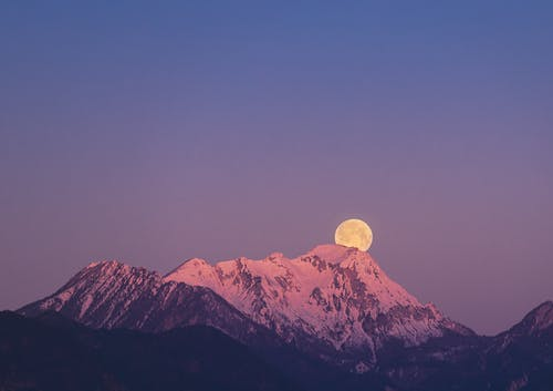 Full Moon Above A Snow Covered Mountain At Dusk