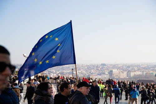 Crowd of people walking on street with waving flag of European Union Courtesy during protest in city against residential buildings