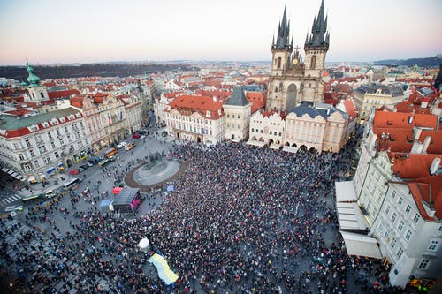 Drone view of crowd of people standing on square near gothic aged church and old town hall located in Prague