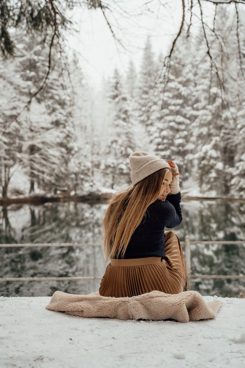 Woman in Black Jacket and Brown Knit Cap Sitting on Brown Wooden Bench