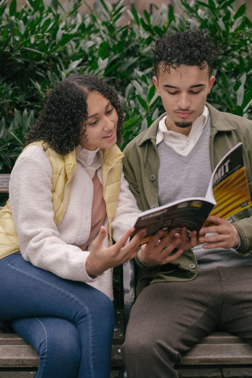 Ethnic couple on bench reading workbook together