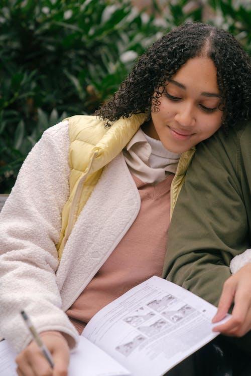 Satisfied ethnic woman writing in workbook in park