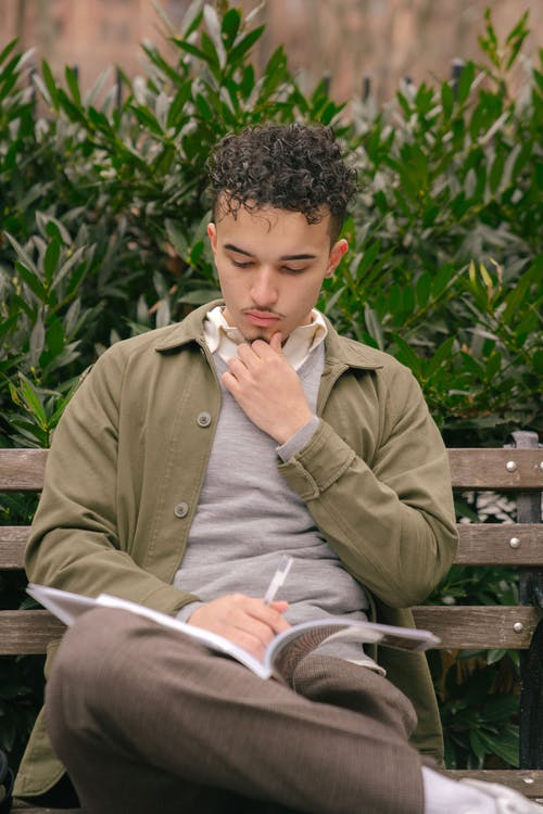 Thoughtful ethnic curly student male in casual outfit sitting on bench and reading textbook while preparing homework in city park at daytime