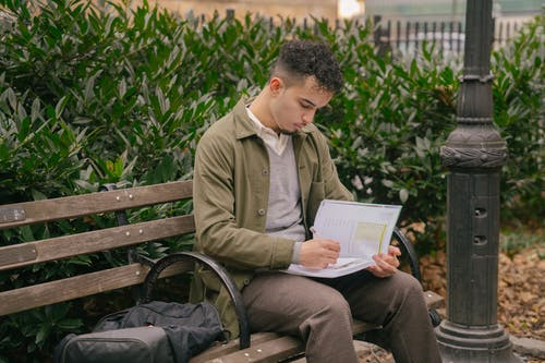 Focused ethnic student doing homework on bench