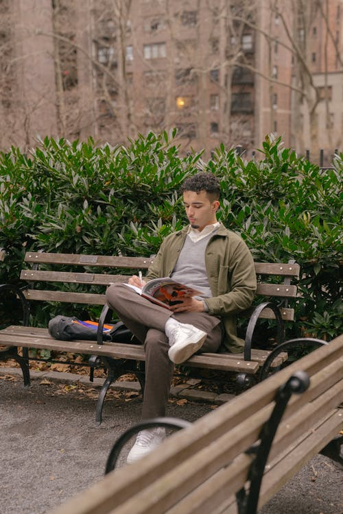 Confident male student doing homework on bench in park