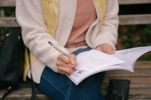 High angle of crop unrecognizable concentrated woman in casual outfit writing in workbook while preparing homework on wooden bench in park at daytime
