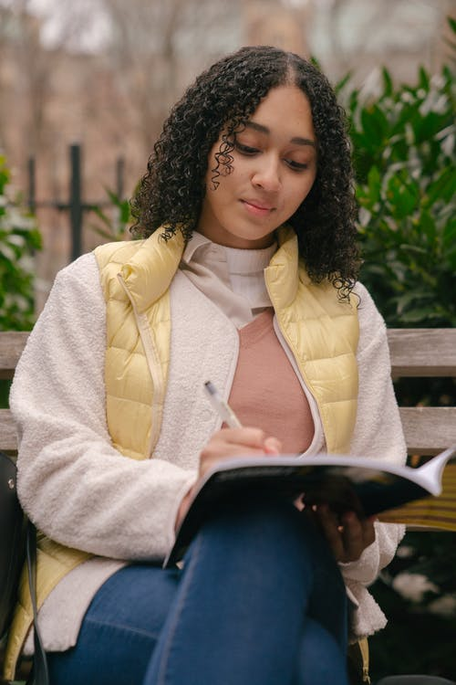From below of focused ethnic curly woman in casual wear sitting with crossed legs on bench in city park while preparing homework