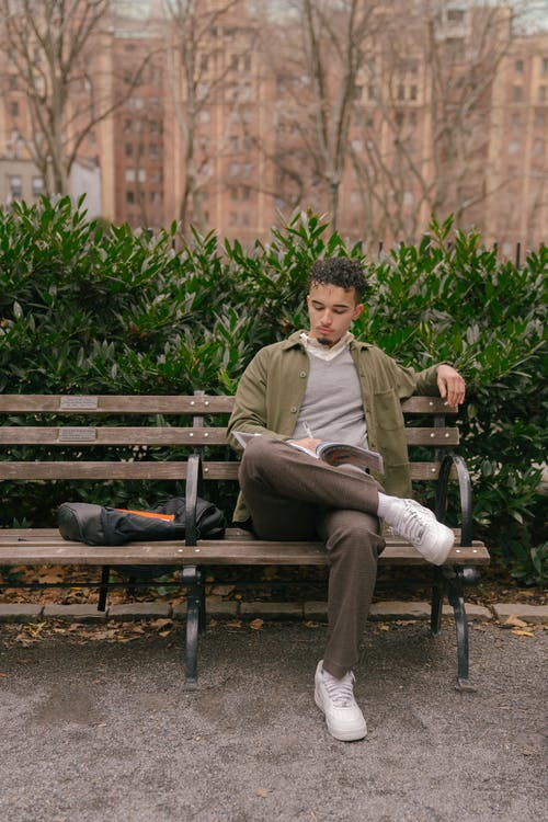 Young man sitting on bench in park with book