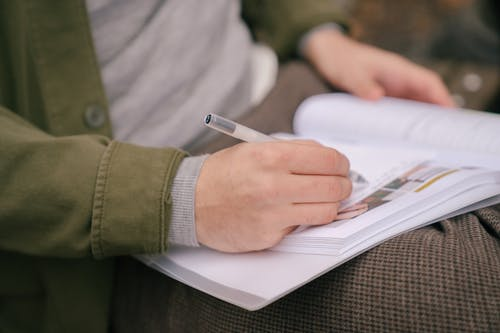 Crop unrecognizable male student in casual clothes writing in workbook while doing homework in park