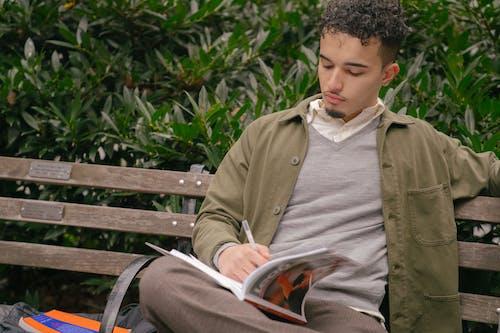 Serious ethnic man doing homework in park