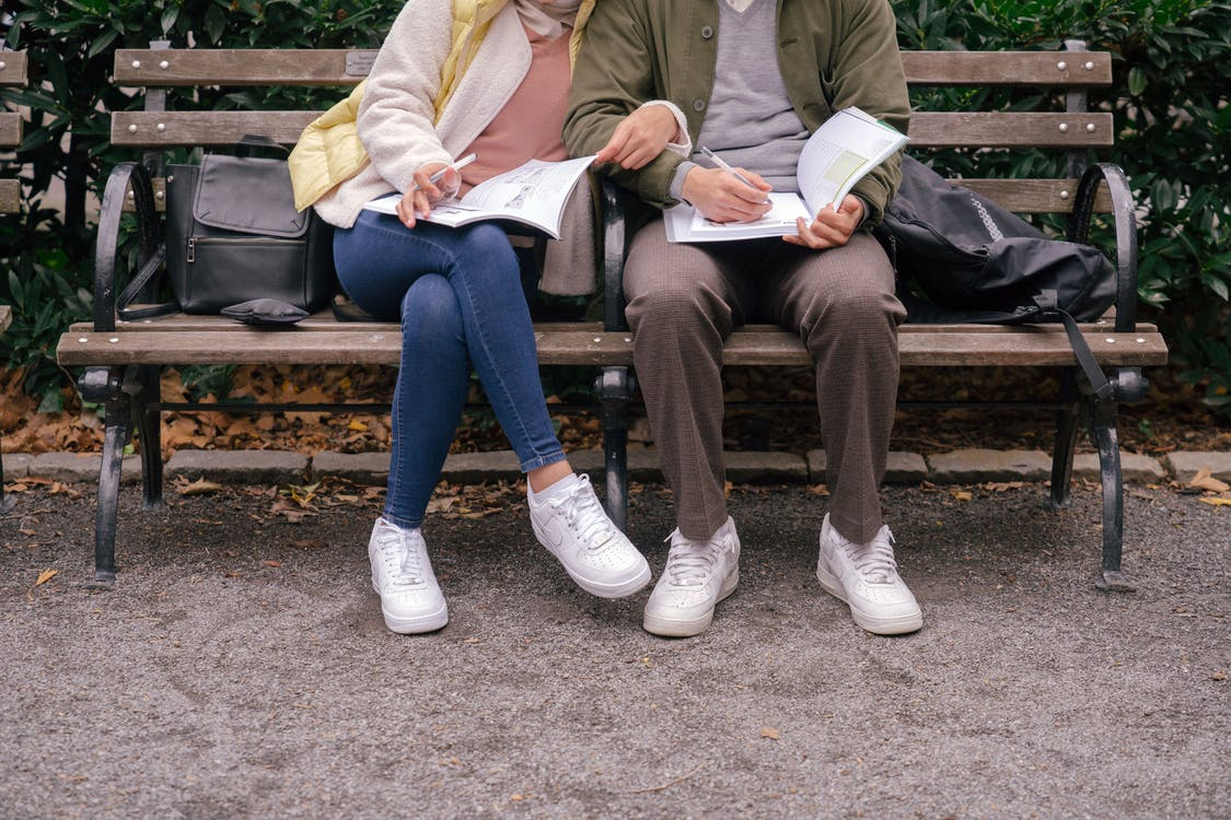 Crop couple in casual clothes and white sneakers sitting on bench in city park while doing homework in workbooks at daytime