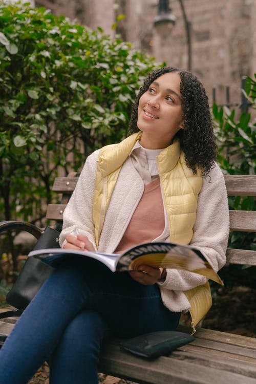 Thoughtful young Hispanic lady in casual outfit sitting with book on wooden bench near purse in park near green bushes while looking away thoughtfully in daylight