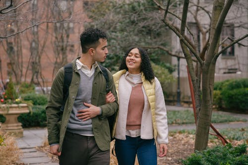 Young Hispanic couple in casual outfit walking in park on walkway while having date and holding hands and looking at each other near bushes and tree in daylight near buildings
