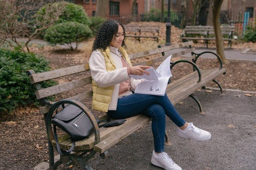 Full length of positive young Latin American female in casual outfit sitting on wooden bench while reading textbook with papers near backpack in street near shrubs and foliage on ground