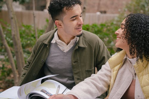 Smiling young Hispanic couple in warm clothes sitting at table while preparing for exams with textbook near green shrubs and trees in daylight in park while looking at each other