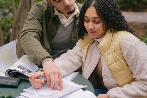 Hispanic couple of friends preparing for exams in park