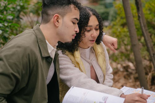 Young Latin American couple in casual outfit studying while taking notes in textbooks on street at table while hugging near bushes and trees in daytime