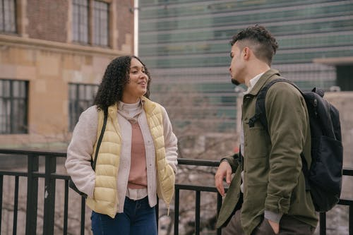 Happy Hispanic girlfriend and boyfriend speaking while leaning on metal railing on street of town