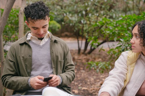 Concentrated Hispanic girlfriend looking at cheerful boyfriend using smartphone