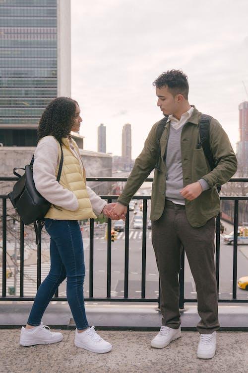 Full body of cheerful ethnic loving couple holding hands near iron railing of urban bridge