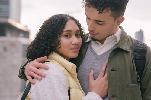 Loving tender Hispanic couple embracing on urban street