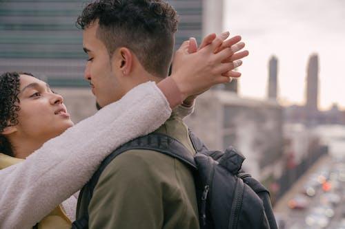 Loving young Hispanic girlfriend hugging boyfriend