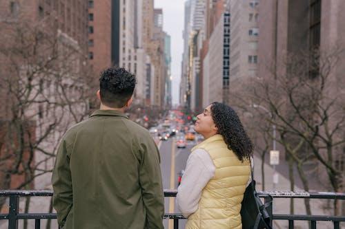 Happy Hispanic girlfriend talking with anonymous boyfriend watching cars rushing on urban road of city