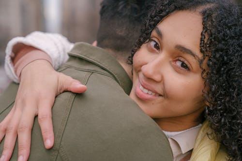 Happy Hispanic woman embracing boyfriend