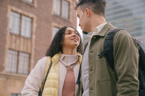 Cheerful Hispanic couple standing on street and looking at each other