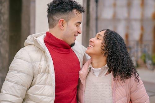 Positive Hispanic couple hugging while walking on street