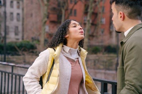 Hispanic couple standing and having quarrel on street