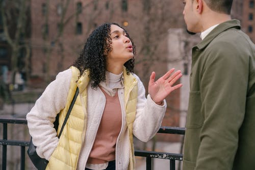 Young stylish Hispanic lady quarreling with crop boyfriend while standing together on city street