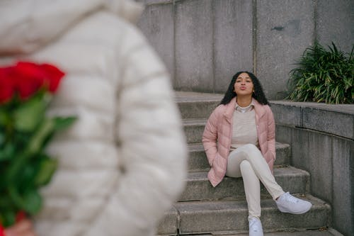Young Hispanic lady pouting lips while waiting for anonymous boyfriend standing with roses bunch