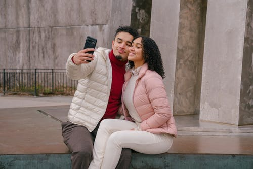 Delighted young ethnic couple touching cheeks while taking selfie sitting on parapet