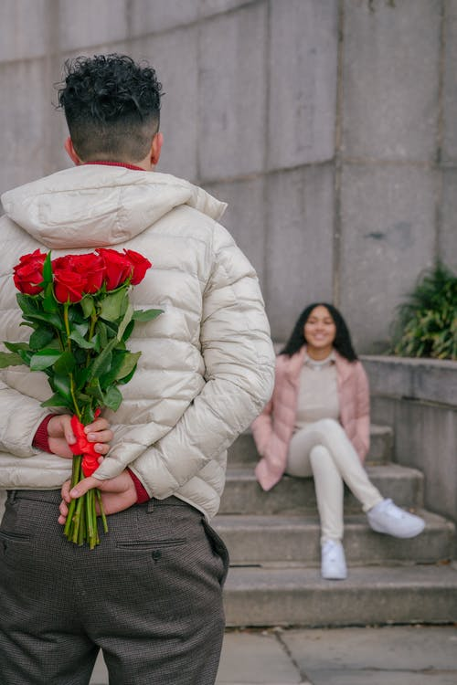 Back view of anonymous guy with curly hair in warm jacket holding bouquet of fresh red roses while standing in front of smiling ethnic girlfriend sitting on stairs in park