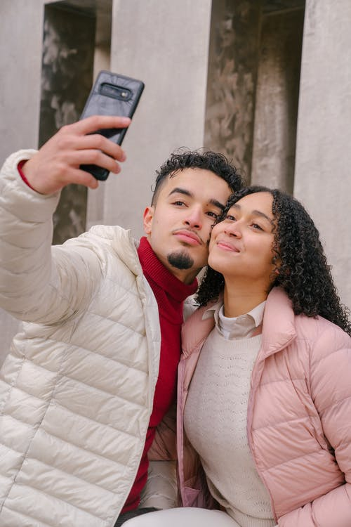 Content young Hispanic couple taking self portrait on mobile phone