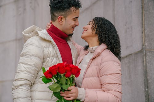 Smiling Hispanic couple with roses bouquet hugging and looking at each other