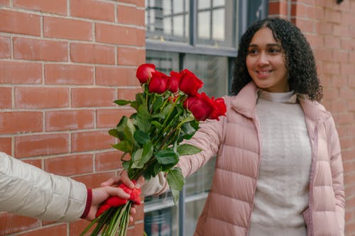 Smiling ethnic woman taking bouquet of roses from hands of crop boyfriend
