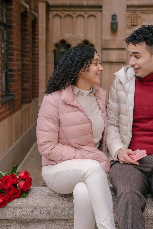 Happy young Hispanic couple talking on bench near aged building in city