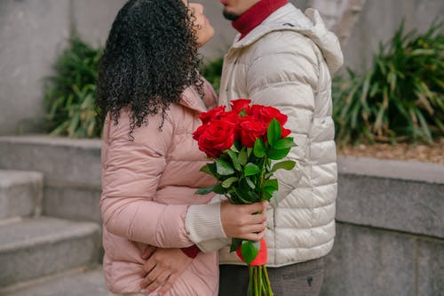Side view of crop couple wearing warm clothes standing close with bunch of tied roses and embracing