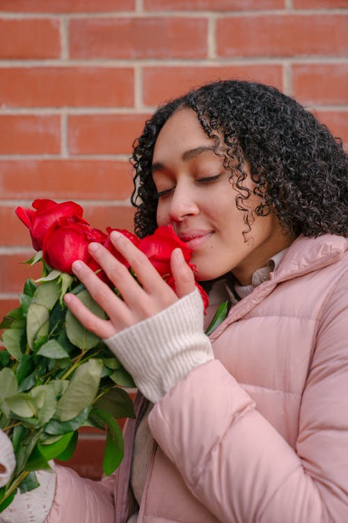 Hispanic female with closed eyes and curly hair wearing outerwear smelling bouquet of fresh roses
