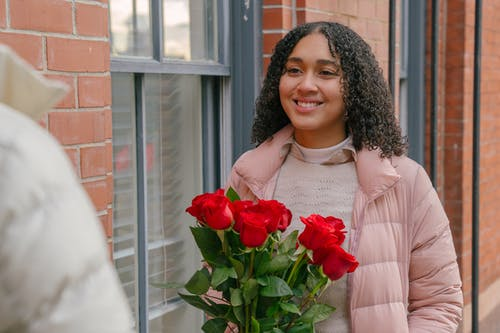 Smiling Hispanic girlfriend with curly hair receiving bunch of fresh flowers from boyfriend for romantic celebration