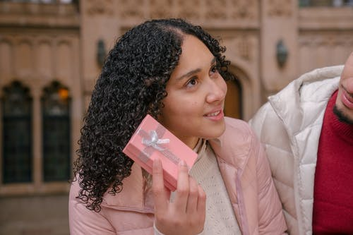 Ethnic woman getting box with surprise from boyfriend