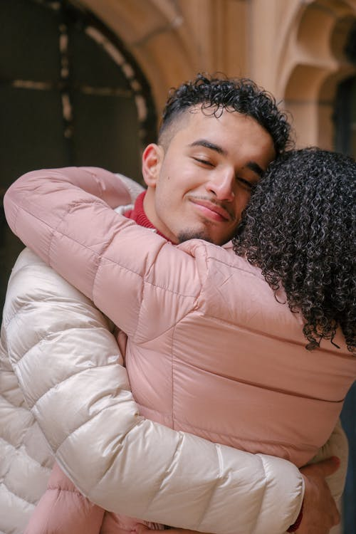 Hispanic boyfriend with closed eyes embracing girlfriend while standing close and enjoying romantic moments