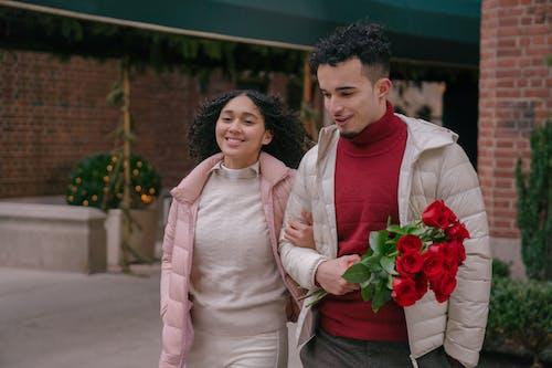 Romantic Hispanic couple walking on street and looking away in daytime