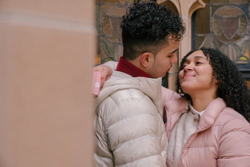 Cheerful Hispanic couple embracing and looking at each other on city street in daytime